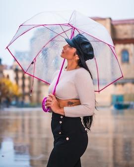 Street style de uma jovem morena latina na chuva da cidade com um guarda-chuva