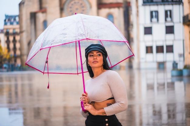 Street style de uma jovem morena na chuva da cidade com um guarda-chuva