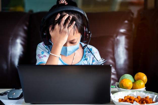 Stress menina da escola é estudar em casa com laptop e máscara facial. conceito de educação on-line