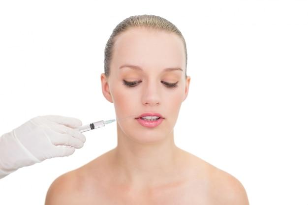Stressed modelo loira bonita recebendo injeção de botox