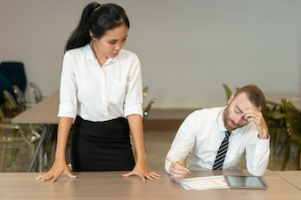 Strict Asian lady controlando subordinado no escritório