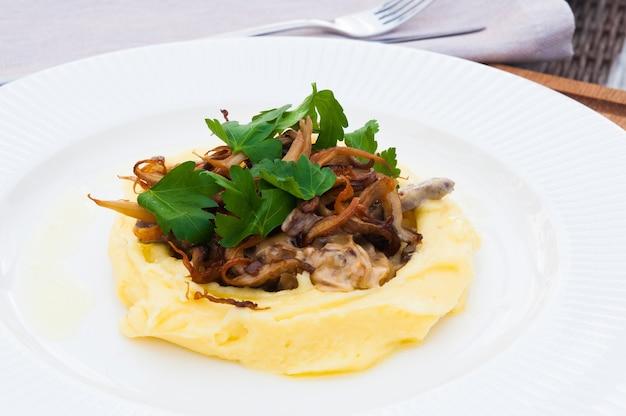 Strogonoff de carne com cogumelos e purê de batata em um prato branco em um restaurante