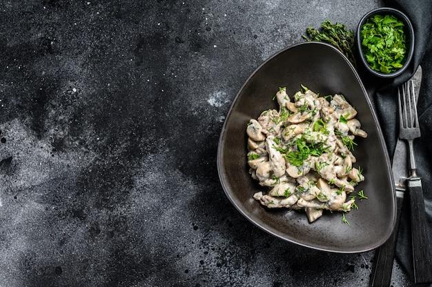 Strogonoff de carne com cogumelos e salsa fresca em um prato na mesa preta.