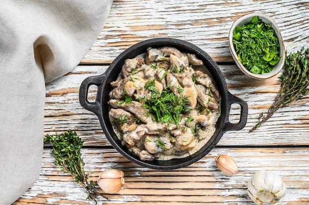 Strogonoff de carne com cogumelos na frigideira na mesa branca.