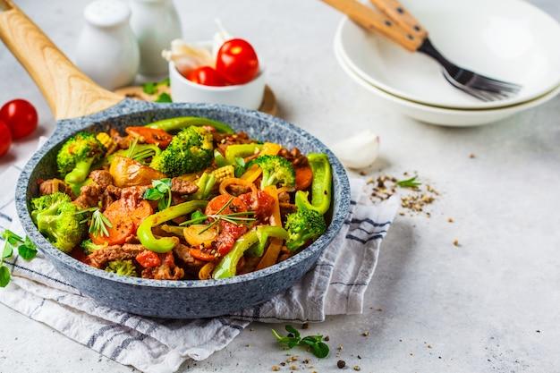Strogonoff de carne frito com batatas e legumes em uma panela.