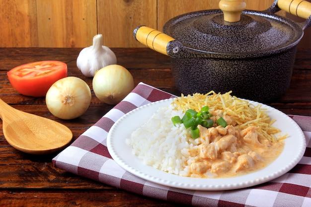 Strogonoff de frango, panela e ingredientes. no brasil, é composto de creme de leite com extrato de tomate, arroz e palitos de batata, sobre mesa de madeira rústica.