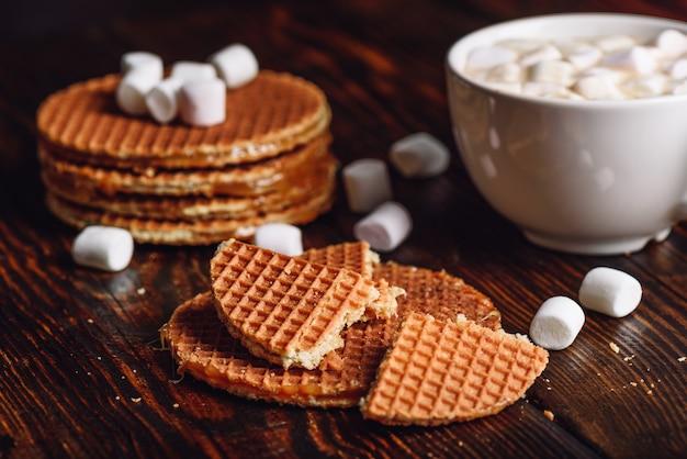 Stroopwafel com quebrado com xícara branca de cacau com marshmallow e pilha de waffles no pano de fundo
