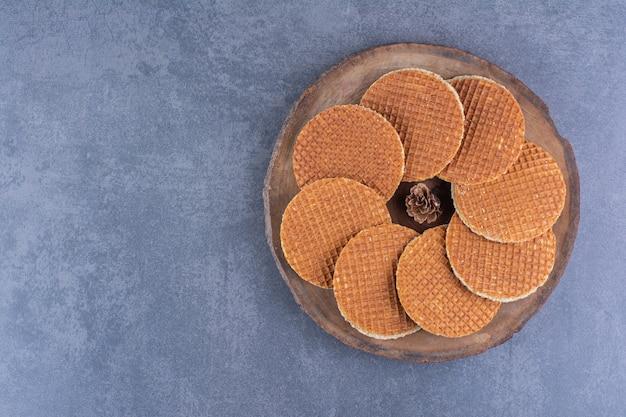 Stroopwafels com pinha isoladas em uma placa de madeira sobre uma superfície de pedra. foto de alta qualidade