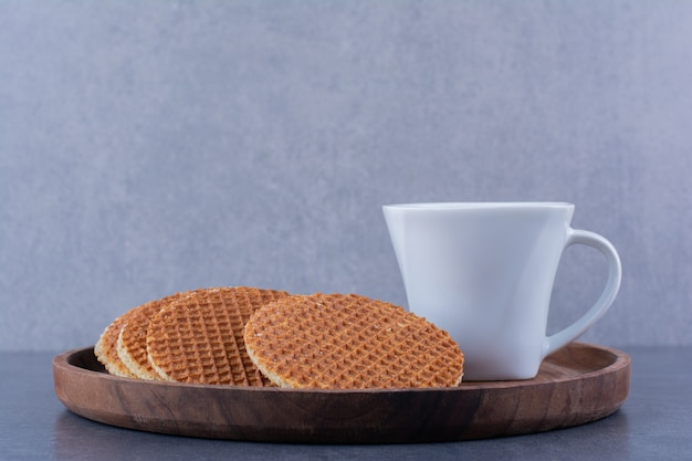 Stroopwafels com uma xícara de chá branca isolada em uma placa de madeira sobre uma superfície de pedra