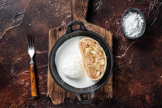 Strudel de apfelstrudel com canela, açúcar de confeiteiro e sorvete de baunilha em uma panela
