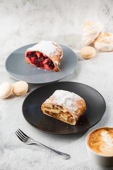 Strudel de maçã austríaco tradicional caseiro com maçãs frescas, nozes e açúcar de confeiteiro. menu para café. pedaço de bolo na chapa preta, copo branco sobre fundo branco de mármore. foto vertical.