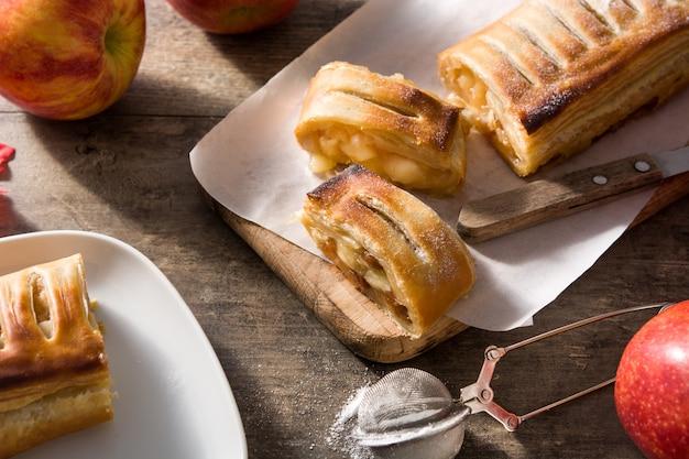 Strudel de maçã caseiro tradicional na mesa de madeira.