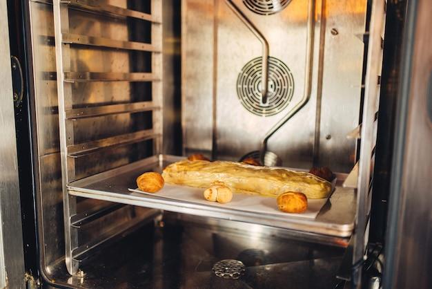 Strudel de maçã clássico na assadeira de metal no forno, ninguém. padaria doce, preparação de sobremesas caseiras