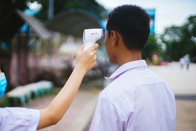 Studen uniforme de verificação de temperatura para proteger o vírus covid-19 ou corona na escola. de volta ao conceito de escola.