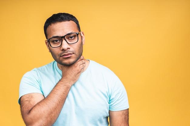 Studio head shot jovem afro-americano negro índio tocando o pescoço, sofrendo de forte dor de garganta, angina. homem infeliz insalubre isolado em fundo amarelo.