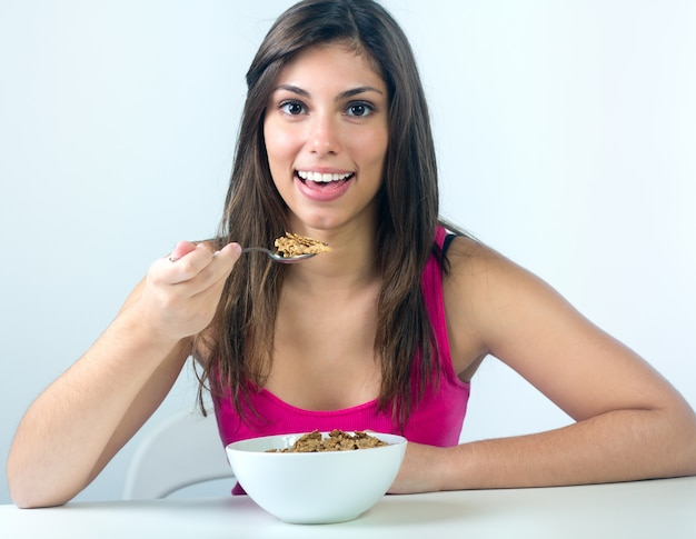 Studio portrait of beautiful young woman eating