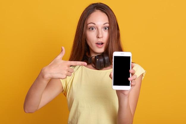 Studio sho de mulher adorável, mostrando o telefone com tela em branco e apontando com o dedo indicador