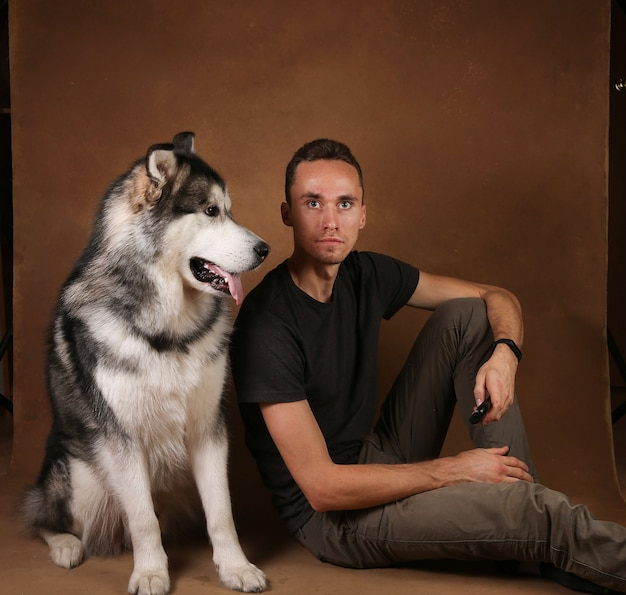 Studo foto de um homem e cachorro malamute do alasca cravando em marrom