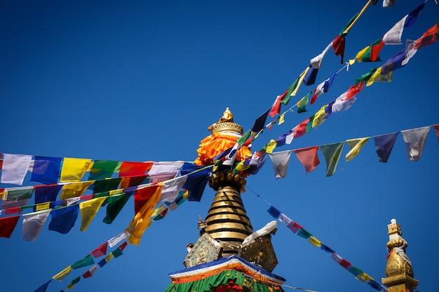 Stupa com bandeiras tibetanas de oração namo buddha,