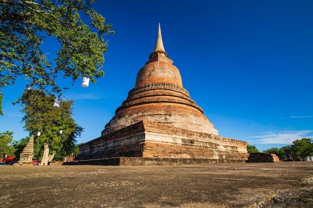 Stupa no templo wat mahathat no parque histórico em sukhothai, céu azul