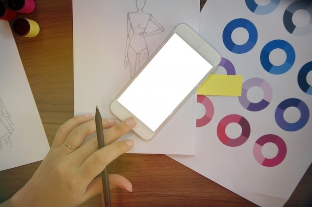 Stylish fashion designer trabalha com tela de espaço em branco do telefone inteligente no atelier. conceito de design criativo
