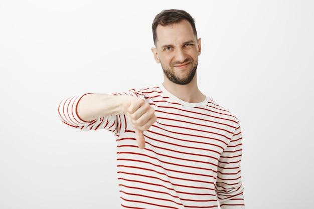 Sua ideia é uma merda. retrato de homem bonito insatisfeito e insatisfeito com barba, fazendo careta de antipatia e mostrando os polegares para baixo, carrancudo