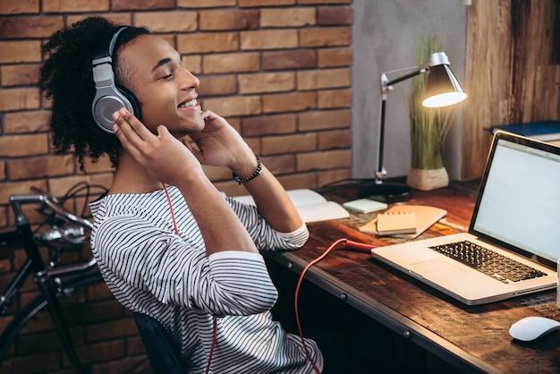Sua música favorita. vista lateral de um jovem africano alegre ajustando os fones de ouvido e mantendo os olhos fechados enquanto está sentado em seu local de trabalho