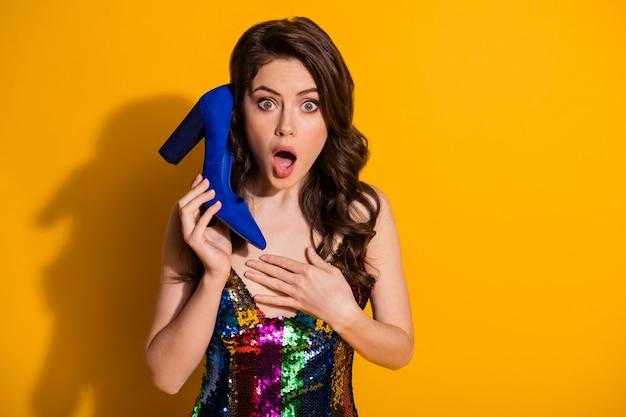 Suas vendas sérias de 50%. menina atônita segurando sapato azul imaginar ela ligar para amigo ouvir notícias da pechincha impressionado usar saia isolada sobre fundo de cor brilhante brilhante