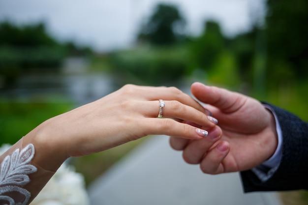 Suaves mãos femininas da noiva com uma aliança de ouro no dedo anelar