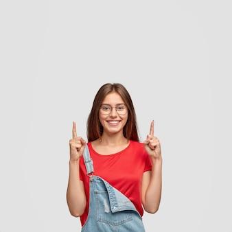 Suba e olhe. mulher caucasiana alegre e emotiva apontando para cima com os dois dedos indicadores