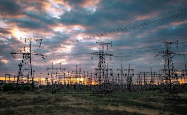 Subestação elétrica com linhas de força e transformadores, ao pôr do sol
