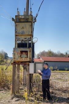 Subestação elétrica, técnico engenheiro eletricista lendo contador de energia elétrica para verificar o consumo.