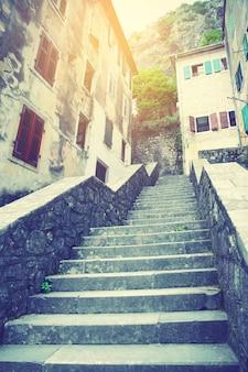 Subida pela rua com escadas na cidade velha de kotor, montenegro. imagem filtrada de estilo retro