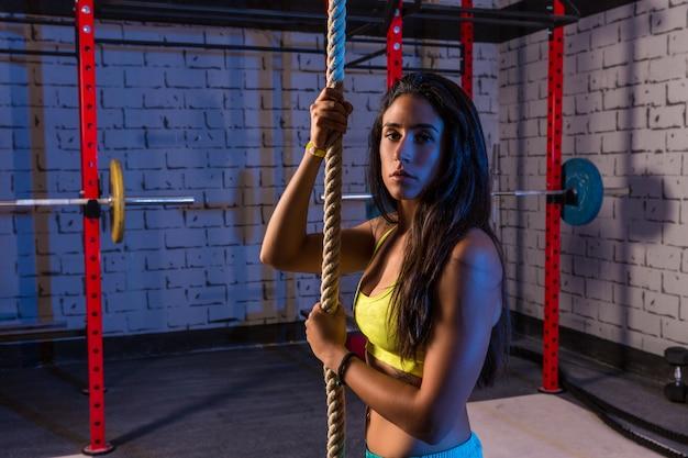 Subir a mulher de exercício de corda no ginásio