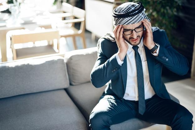 Sublinhou o empresário árabe no sofá no quarto de hotel