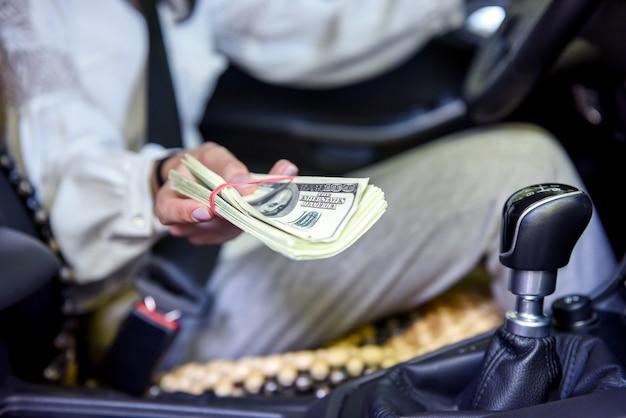 Suborno. mulher sentada no banco do motorista dando um pacote de dólares