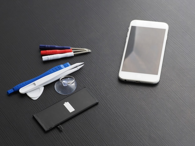 Substituindo a bateria de um smartphone antigo. ferramentas, smartphone e bateria em uma mesa de madeira.