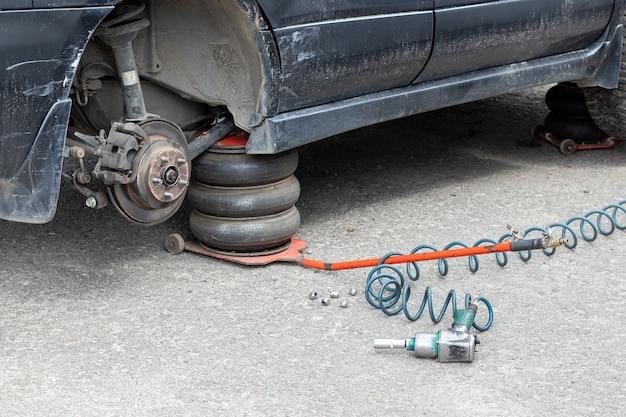 Substituindo a roda no centro de serviço de pneus. carro preto sujo sem roda levantado no macaco pneumático em uma oficina mecânica