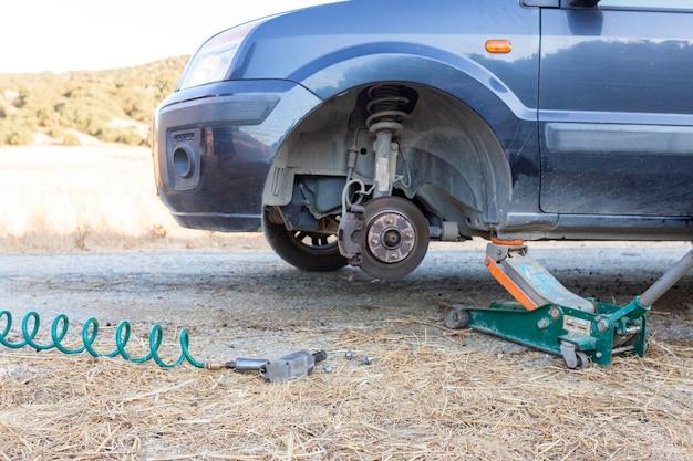 Substituindo as rodas danificadas e substituindo por novas, a roda do carro quebrou no campo em uma estrada