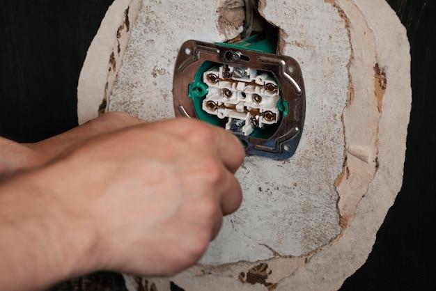 Substituindo e instalando uma nova tomada elétrica. mãos com um eletricista de homem chave de fenda