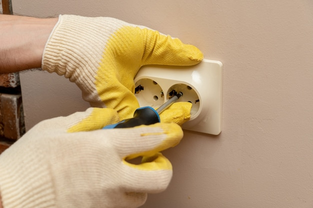 Substituindo, instalando uma tomada elétrica, tomada com as mãos em luvas de borracha de proteção