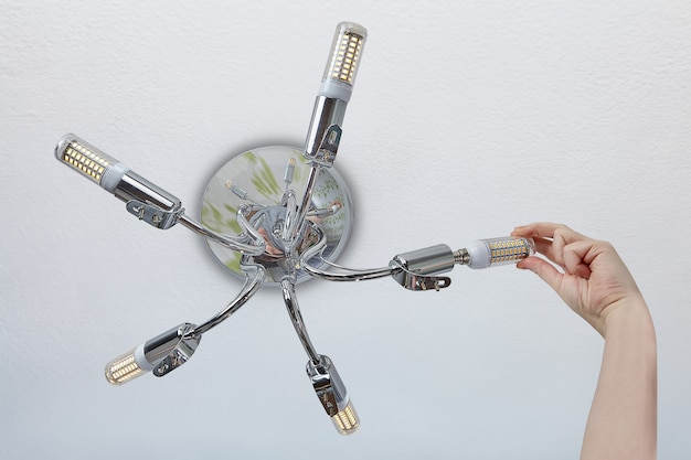 Substituindo lâmpadas em luminárias domésticas, a mão feminina instala uma lâmpada led de milho no suporte da lâmpada.