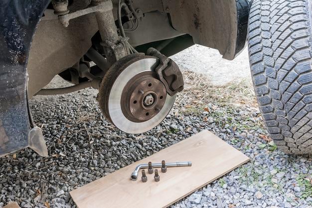 Substituindo uma roda quebrada em uma estrada de terra ao ar livre