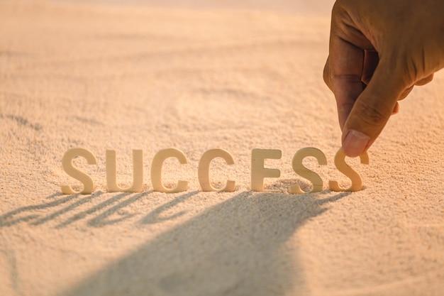 Sucesso - conceito de motivação empresarial com alfabeto de madeira, colocar na praia de areia. inspiradora citação. palavras motivacionais