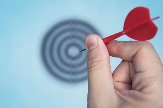 Sucesso da educação empresarial e conceito de alvo. feche uma mão está mirando a seta verde do dardo em direção ao centro do alvo. atinja o alvo. sucesso nos negócios.