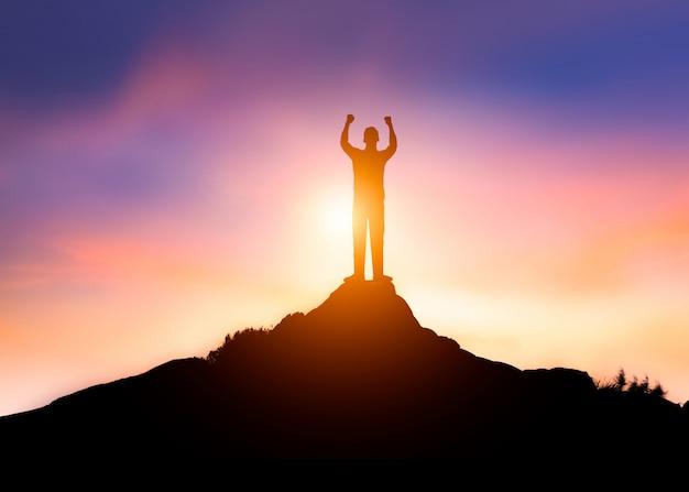 Sucesso de empresário ou vencedor no topo da montanha de rochas ao pôr do sol, conceito de líder