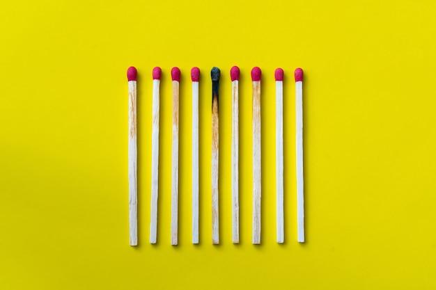 Sucesso, derrota, conquista. o conceito de felicidade. fósforos em um fundo amarelo. fósforo escuro queimado entre fósforos normais. acendendo fósforo aceso para seus vizinhos, uma metáfora para ideias e inspiração