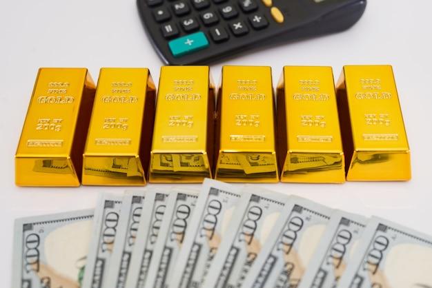 Sucesso do investimento ou conceito de cálculo de riqueza financeira, barras de ouro / barras de ouro em uma pilha de notas de dinheiro de dólares americanos com calculadora.