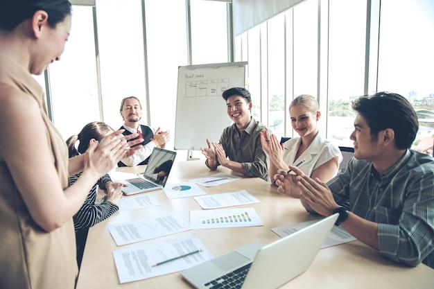 Sucesso dos empresários do grupo com palmas juntos na sala de reuniões.