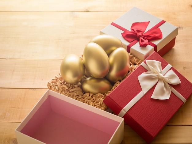 Sucesso financeiro. ovo de ouro em uma caixa de presente vermelha